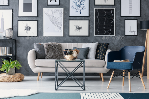Blue armchair next to sofa and table in living room interior wit .