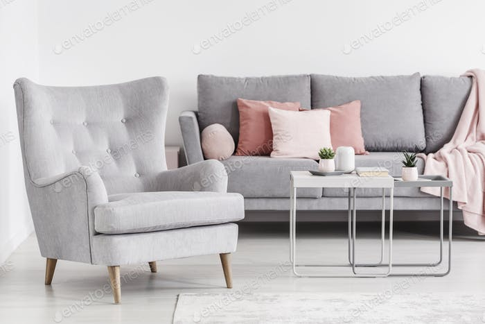 Comfy armchair and grey sofa with pink pillows, and coffee table .