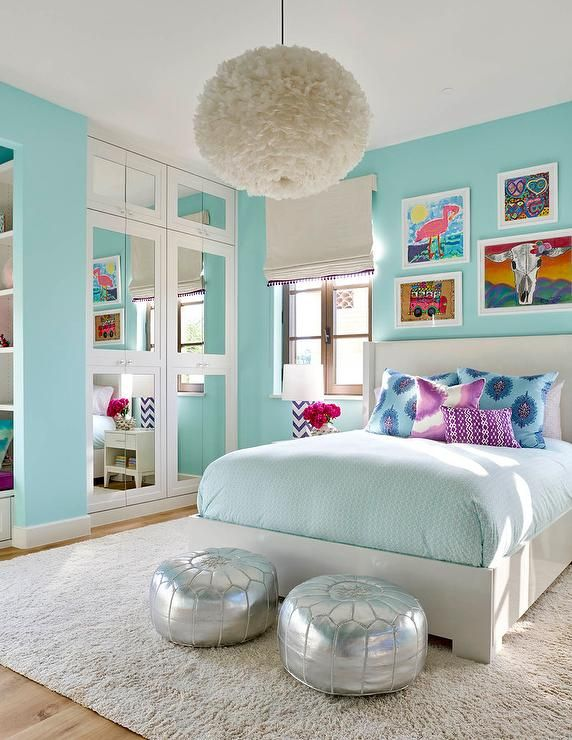 Turquoise blue girl's bedroom features a white feather chandelier .