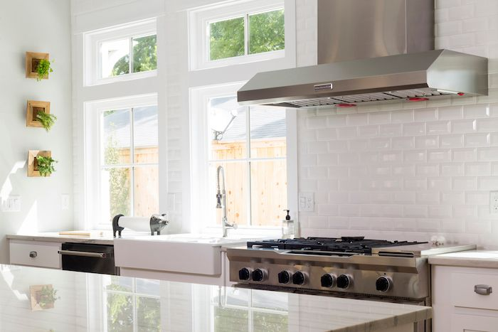 A classic yet modern kitchen featuring beveled white subway tile .