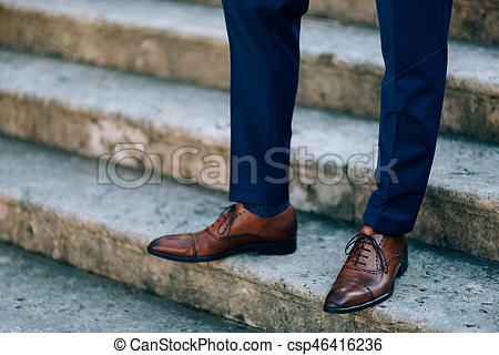 Brown shoes on male legs. the groom in a blue pant